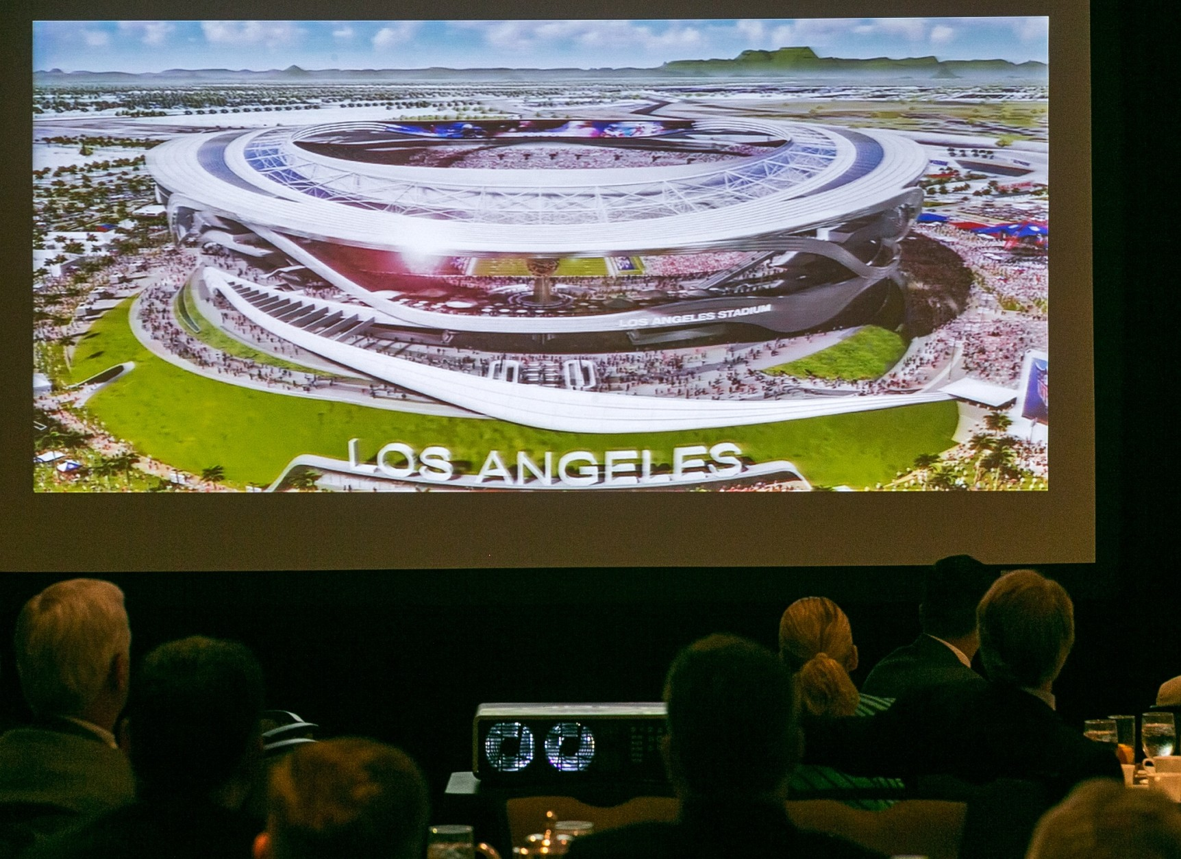 An architectural rendering for a new NFL stadium is projected during a lunch sponsored by the Los Angeles Sports Council downtown Los Angeles Monday, Aug. 17, 2015. The $1.7-billion new NFL football stadium proposed for Carson by the owners of the San Diego Chargers and Oakland Raiders will be located 15 miles from West Los Angeles, 10 miles from Orange County and 12 miles from downtown. The stadium's capacity will be 65,000 and can be increased to 75,000 for the Super Bowl. (AP Photo/Damian Dovarganes)