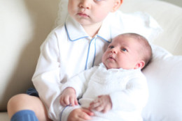 This image made available by Kensington Palace Saturday, June 6, 2015, taken by Kate, Duchess of Cambridge, at Amner Hall, eastern England in mid-May 2015 shows Britain's Princess Charlotte, right, being held by her brother, 2-year-old, Prince George. Britain's royals have been photographed by some of the world's leading photographers. But Prince William and Kate are continuing a more informal tradition begun two years ago with the first official portrait of Prince George, taken by his grandfather Michael Middleton. Charlotte was born May 2 and is fourth in line to the throne. (Duchess of Cambridge via AP)  MANDATORY CREDIT