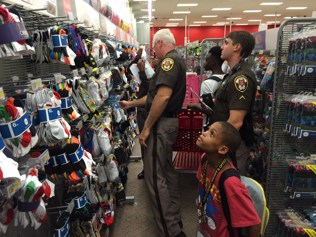 Pictured with his helpers, Captain Sean Whitmore and PFC Ulsh, rising fourth-grader Dontay Scott like movie themes -- he chose 'Star Wars' high-top sneakers and socks depicting Minions characters. (WTOP/Kristi King)