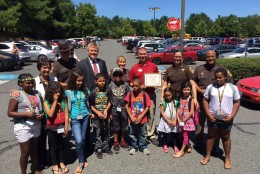 Just some of the 40 homeless children being treated to a shopping spree pose with Sheriff's deputies and community leaders, including Fairfax County Supervisors Chair Sharon Bulova, Supervisor John Cook, Sheriff Stacey A. Kincaide and Nathan Cooke of Target. (WTOP/Kristi King)