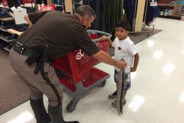 """Rising fourth-grader Dontay Scott shows off his Tae Kwan Do skills and receives a congratulatory high-five from Fairfax County's sheriff, who says """"He's one of our Junior Deputies now."""" (WTOP/Kristi King)"""