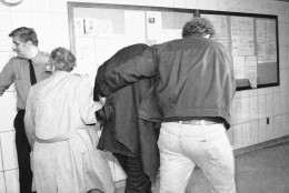 A man believed to be Mark David Chapman, covered center, is hustled from a New York City police station, to be booked at headquarters, Tuesday, Dec. 9, 1980. Chapman is expected to be charged in the murder of former Beatle John Lennon in New York last night. (AP Photo/Handshuh)