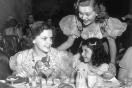 circa 1935:  American singer and actress Judy Garland seated, left, at a children's tea party.  (Photo by Hulton Archive/Getty Images)