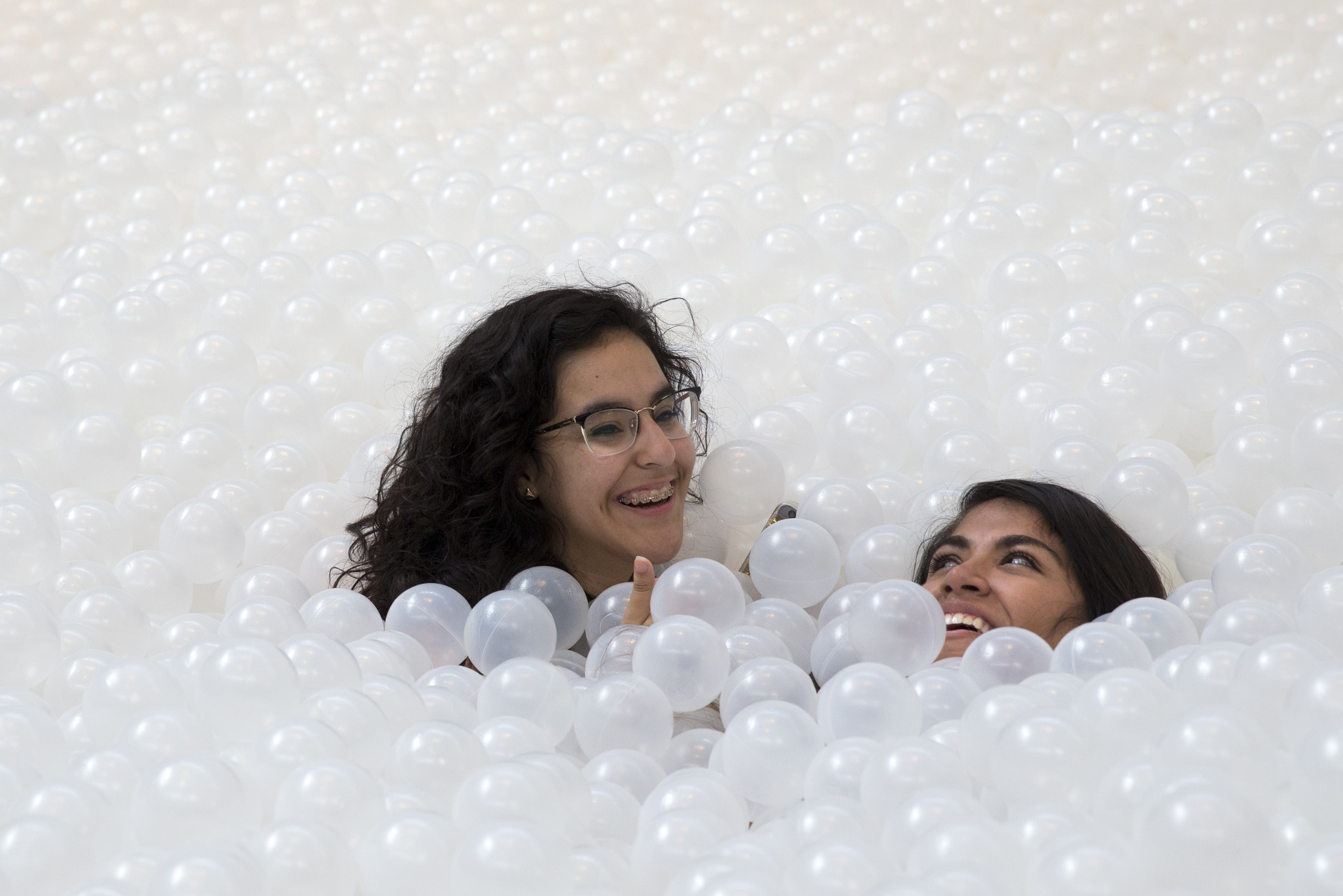 "Girls submerge in the ocean at  ""The Beach"", an interactive architectural installation inside the National Building Museum in Washington, Wednesday, July 29, 2015. The Beach, which spans the length of the museum's Great Hall, was created in partnership with Snarkitecture, and covers 10,000 square feet and includes an ""ocean"" of nearly one million recyclable translucent plastic balls.  (AP Photo/Carolyn Kaster)"
