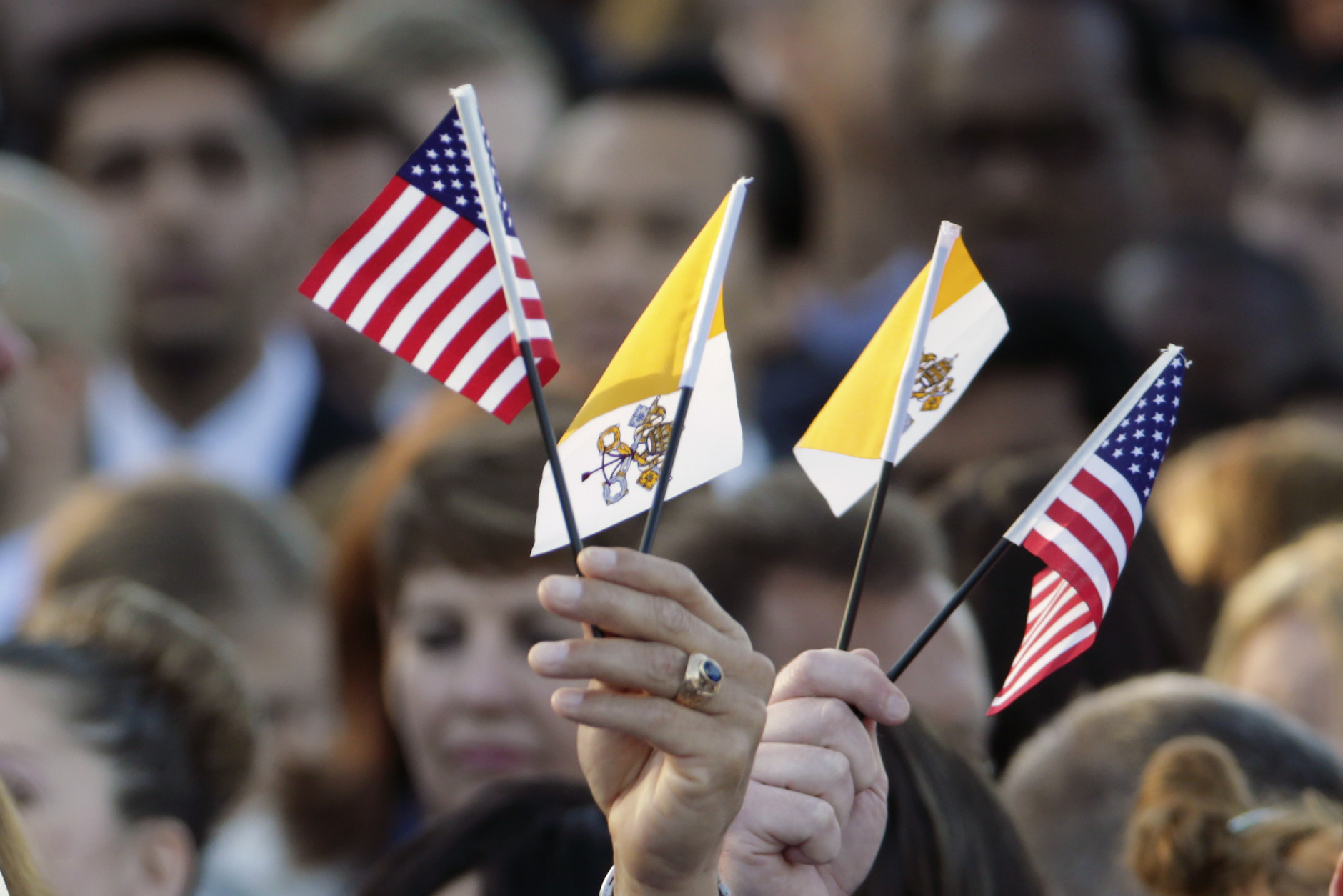 Spectators hoping for a glimpse of Pope Francis waves Papal and U.S. Flags on the South Lawn of the White House in Washington, Wednesday, Sept. 23, 2015, before the official state arrival ceremony where President Barack Obama will welcome the pope. (AP Photo/Pablo Martinez Monsivais)