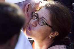A woman reacts as Pope Francis hugs her as he departs the Apostolic Nunciature, the Vatican's diplomatic mission in Washington, Wednesday, Sept. 23, 2015, en route to the White House where President Barack Obama will hot a state arrival ceremony.  (AP Photo/Cliff Owen)