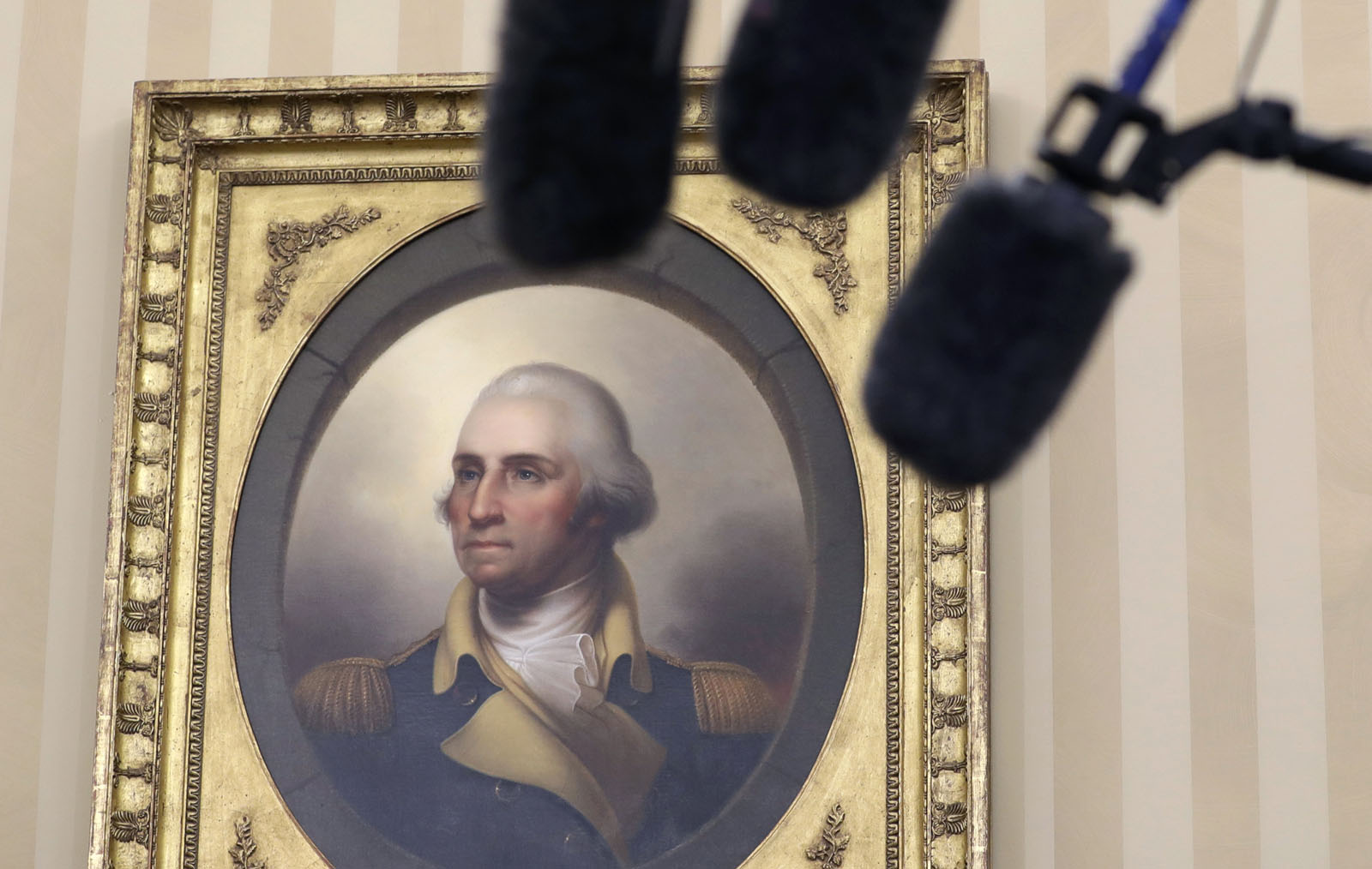A portrait of George Washington and media microphones are seen in the Oval Office in Washington, Friday, Sept. 16, 2016, as President Barack Obama talks to media at the start of a meeting with business, government, and national security leaders on how the Trans-Pacific Partnership can benefit American workers and businesses and further national security. (AP Photo/Carolyn Kaster)