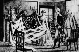 Bestsy Ross shows the first American flag she made to George Washington and his aides in her Arch Street home in Philadelphia in 1776. A year later the continental Congress formally adopted the 13- stripe, 13 -starflag of red, White, and blue. (AP Photo)