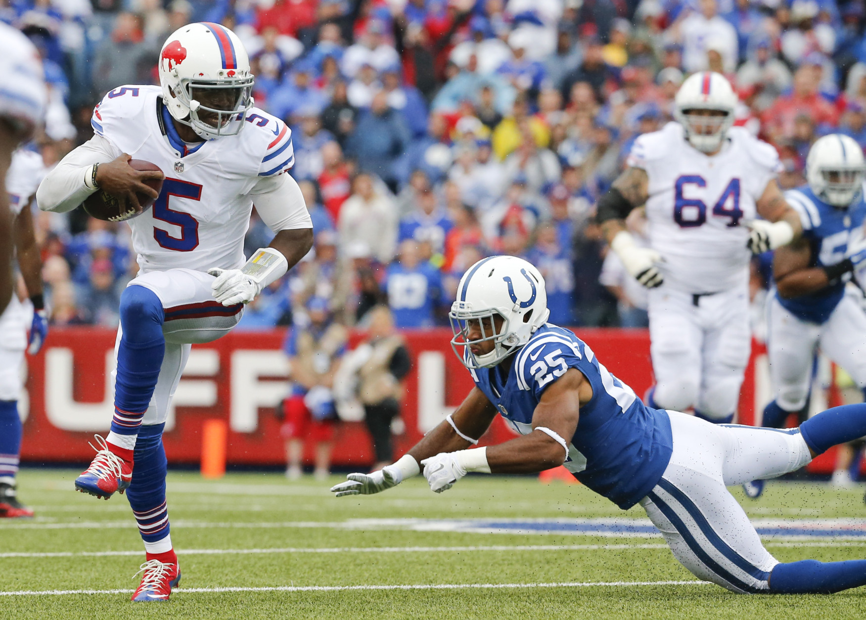 Buffalo Bills quarterback Tyrod Taylor (5) eludes Indianapolis Colts defensive back Jalil Brown (25) during the first half of an NFL football game on Sunday, Sept. 13, 2015, in Orchard Park, N.Y. (AP Photo/Bill Wippert)