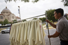A worker pulls a rack of vestments to be worn by priests at Wednesday's Mass with Pope Francis during preparations at the Basilica of the National Shrine of the Immaculate Conception, rear, Monday, Sept. 21, 2015, in Washington. Pope Francis will celebrate Mass Wednesday at the basilica, the largest Catholic church in the United States and North America, with a crowd of about 30,000. (AP Photo/David Goldman)