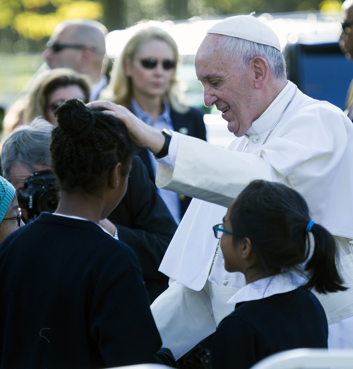 Pope Francis places his hand on the head of a girl as he greets school children prior to departing the Apostolic Nunciature, the Vatican's diplomatic mission in the heart of Washington, Wednesday, Sept. 23, 2015. Pope Francis will visit the White House, becoming only the third pope to visit the White House.  (AP Photo/Cliff Owen)