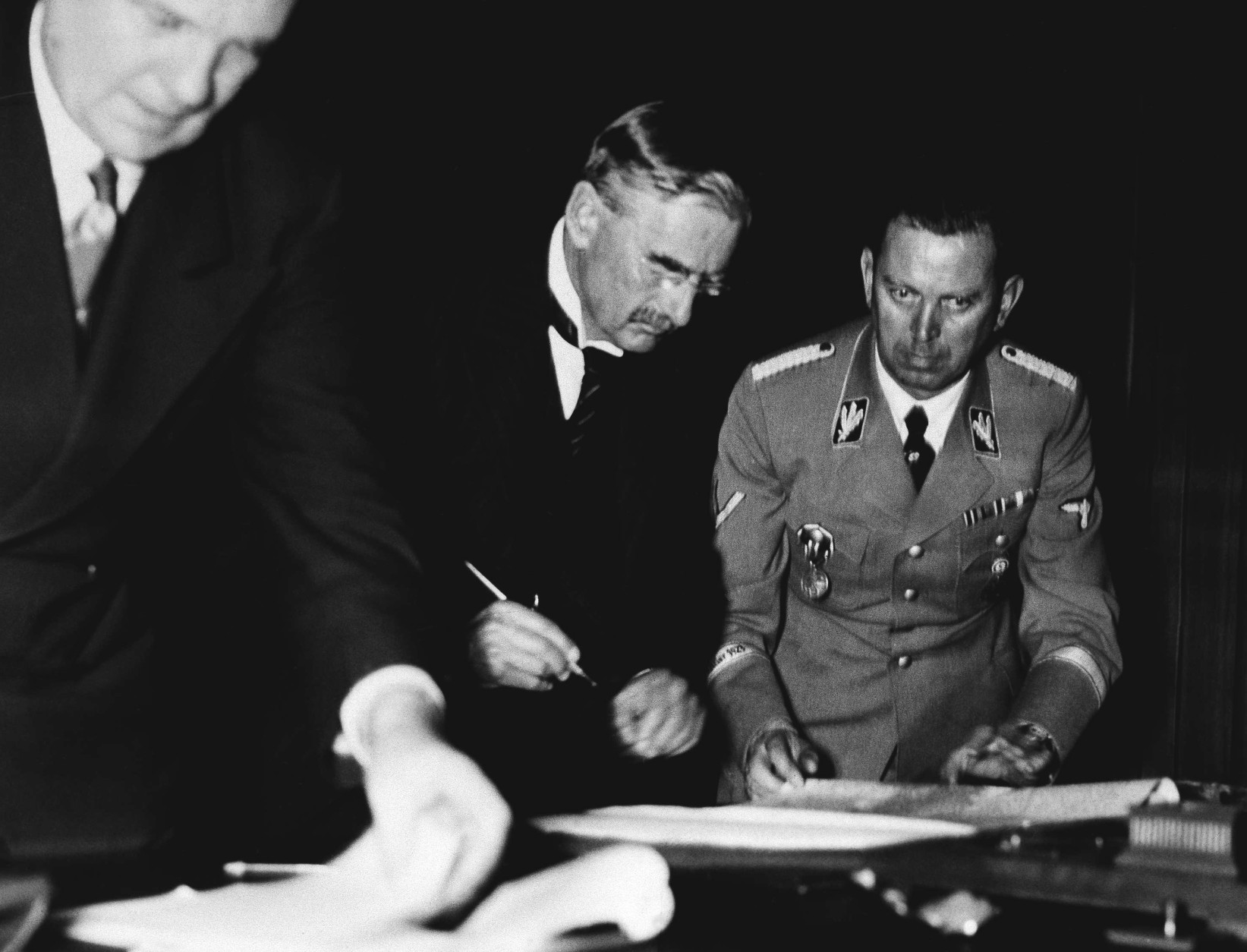 After long discussions the treaty for giving the Sudeten Districts from Czechoslovakia back to Germany was signed by the four statesmen Adolf Hitler, Benito Mussolini, Eduard Daladier and Sir Neville Chamberlain at the Fuehrerhouse at Munich on Sept. 30, 1938. Premier Neville Chamberlain rears the treaty over before signing. Left interpreter Dr. Paul Schmidt, Sir Neville Chamberlain and Hitler?s adjutant brigade leader Schaub. (AP Photo/Berlin Hoffman)