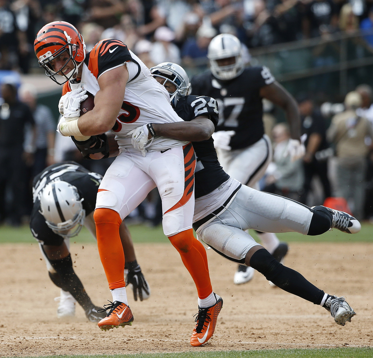 Cincinnati Bengals tight end Tyler Eifert (85) runs as Oakland Raiders cornerback Charles Woodson (24) tries to tackle him during the first half of an NFL football game in Oakland, Calif., Sunday, Sept. 13, 2015. (AP Photo/Tony Avelar)