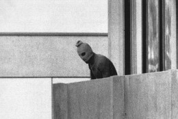 FILE - In this Sept. 5, 1972, file photo, a member of the Arab Commando group which seized members of the Israeli Olympic Team at their quarters at the Munich Olympic Village appears with a hood over his face on the balcony of the village building where the commandos held several members of the Israeli team hostage.  (AP Photo/Kurt Strumpf, File)