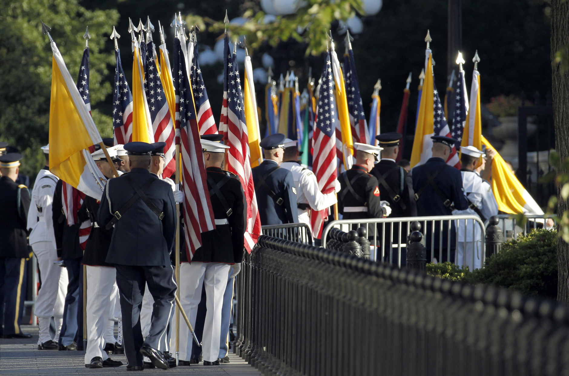 Members of the armed services carry U.S. and Vatican flags into the White House in Washington, Wednesday, Sept. 23, 2015, for the upcoming visit by Pope Francis. (AP Photo/Alex Brandon/Pool)