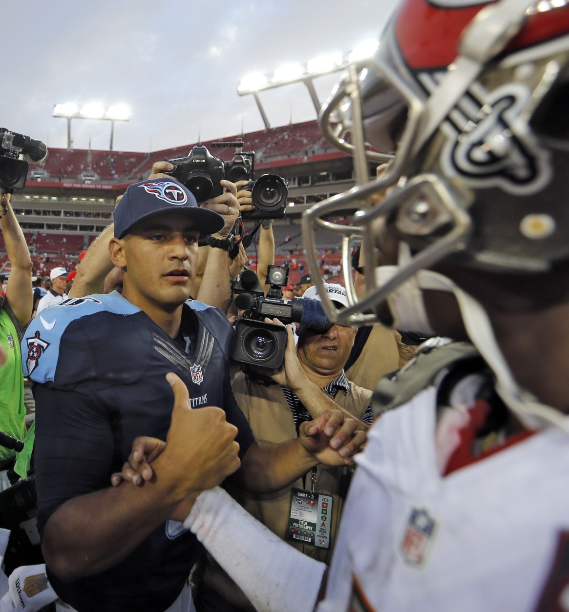 Tennessee Titans quarterback Marcus Mariota, left, shakes hands with Tampa Bay Buccaneers quarterback Jameis Winston after the Titans defeated the Buccaneers 42-14 during an NFL football game Sunday, Sept. 13, 2015, in Tampa, Fla. (AP Photo/Scott Audette)