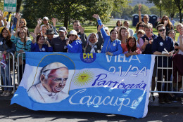 People wave and cheer on the parade for Pope Francis, Wednesday, Sept. 23, 2015, in Washington. Earlier, President Barack Obama hosted the pope at the White House during a state arrival ceremony. (AP Photo/Alex Brandon, Pool)