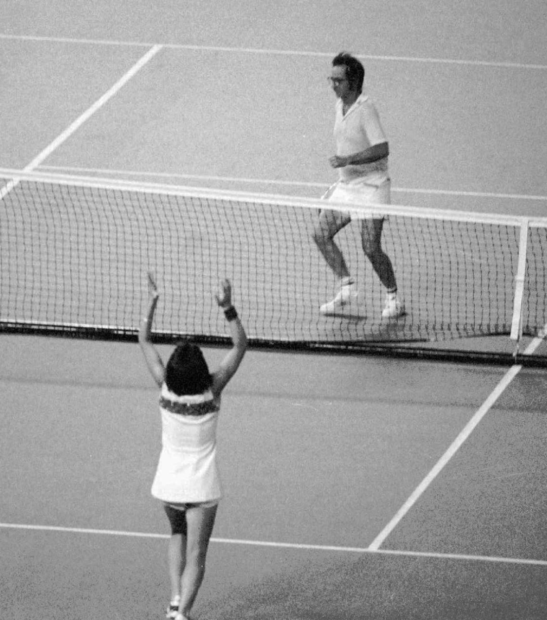"FILE - In this Sept. 20, 1973 file photo. Billie Jean King raises her arms after defeating Bobby Riggs, rear, getting ready to jump over the net, in the ""Battle of the Sexes"" at the Houston Astrodome. King believes Caitlyn Jenner has given people clarity about transgender issues beyond the progress already seen four decades after they shared the international spotlight as athletes.  (AP Photo, File)"