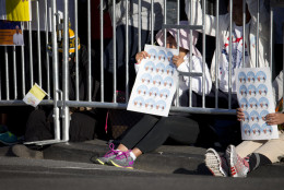 Women hold images Pope Francis as they gather behind fencing along the parade route around the Ellipse in Washington, Wednesday, Sept. 23, 2015. (AP Photo/Carolyn Kaster)