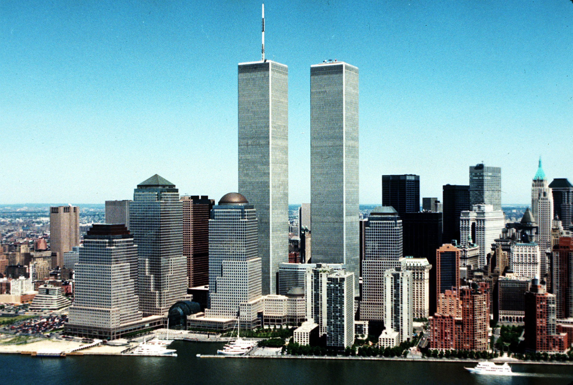FILE - In this 1990 file photo, New York City skyline with World Trade Center's twin towers in the center. Before the towers crumbled, before the doomed people jumped and the smoke billowed and the planes hit, the collective American memory summoned one fleeting fragment of beauty: a clear blue sky. (AP Photo, File)