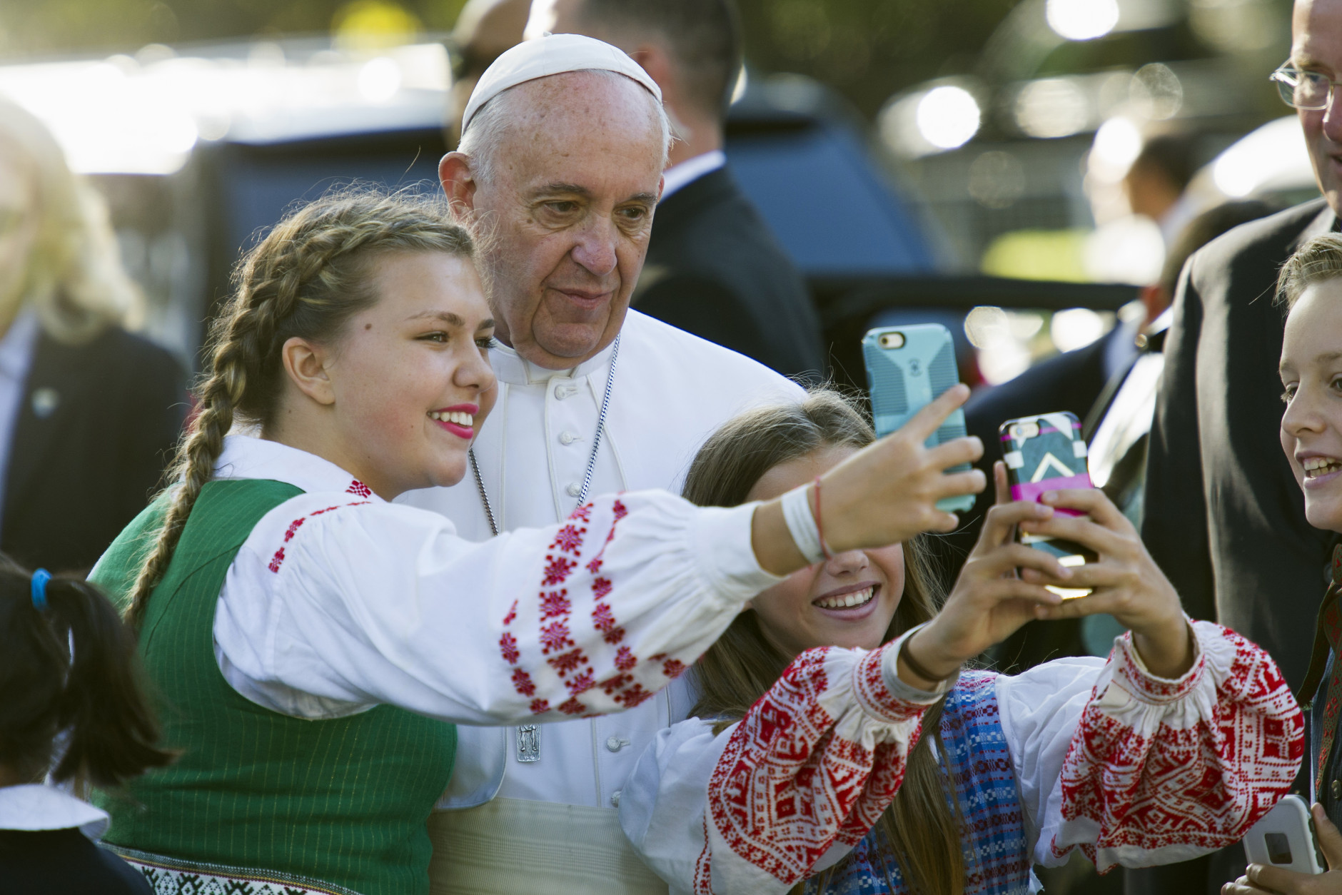Children of parents who work at the Lithuanian Embassy take selfies with Pope Francis as he departs the Apostolic Nunciature, the Vatican's diplomatic mission in Washington, Wednesday, Sept. 23, 2015. Pope Francis will visit the White House where President Barack Obama will host a state arrival ceremony.  (AP Photo/Cliff Owen)