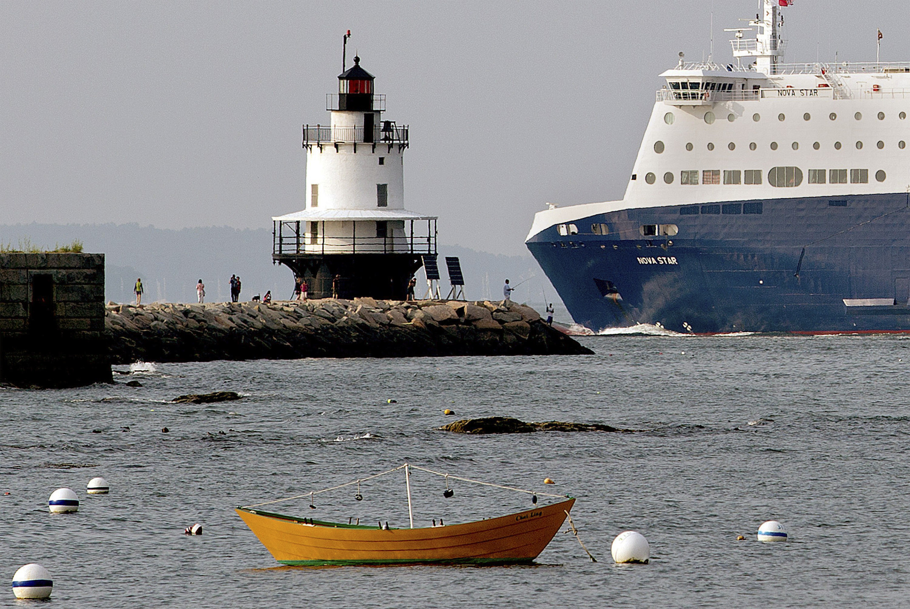 In this July 13, 2015 photo, the Nova Star ferry travels past fishermen and tourists near the Spring Point Ledge Light on its way to the Ocean Gateway terminal in Portland, Maine. With the decline of groundfishing and freight shipping, Maine's largest city increasingly relies on tourists passing through its port. (Gabe Souza/Portland Press Herald via AP) MANDATORY CREDIT