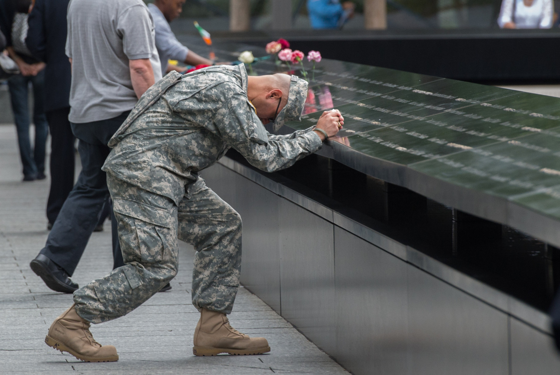 Army Sgt. Edwin Morales prays during a ceremony at the World Trade Center site in New York on Friday, Sept. 11, 2015. With a moment of silence and somber reading of names, victims' relatives began marking the 14th anniversary of Sept. 11 in a subdued gathering Friday at ground zero.(AP Photo/Bryan R. Smith)