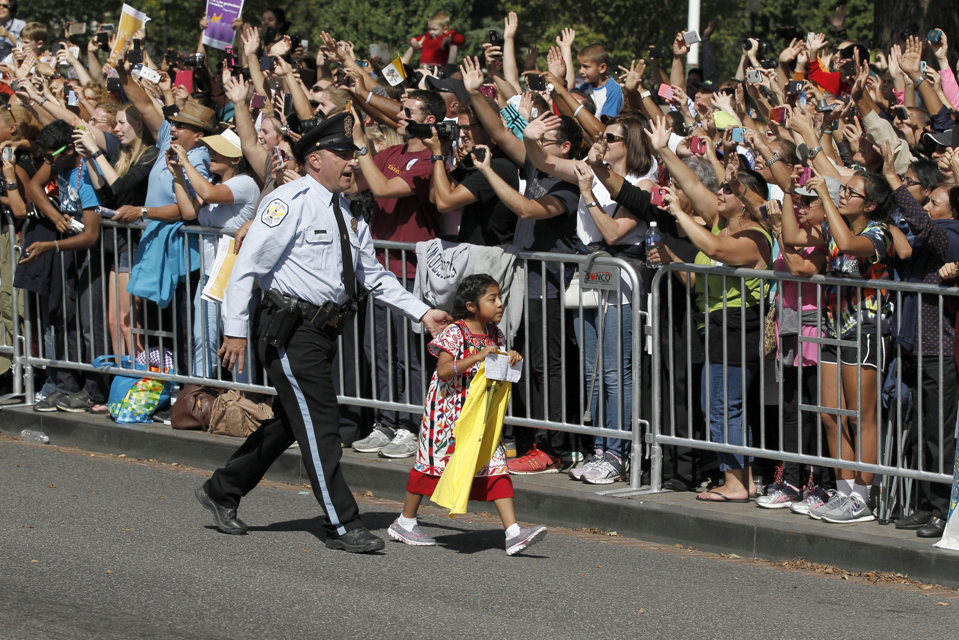 A child is escorted back before Pope Francis called for the child to be brought to him, during a parade in Washington, Wednesday, Sept. 23, 2015. (AP Photo/Alex Brandon, Pool)
