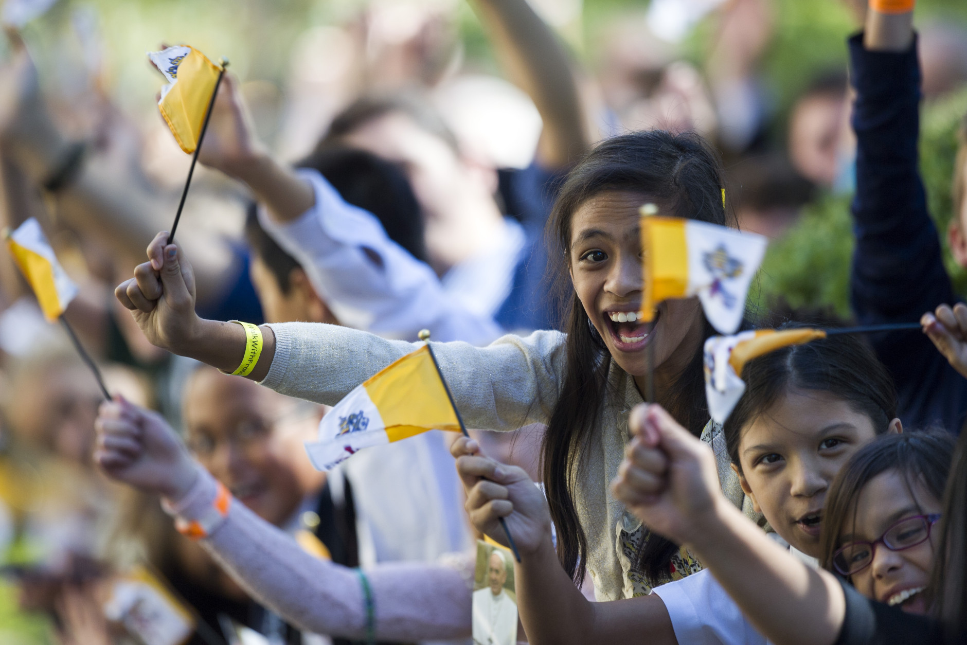 School girls wave Papal flag as Pope Francis' motorcade arrives at the Apostolic Nunciature, the Vatican's diplomatic mission in Washington, Wednesday, Sept. 23, 2015.  (AP Photo/Cliff Owen)