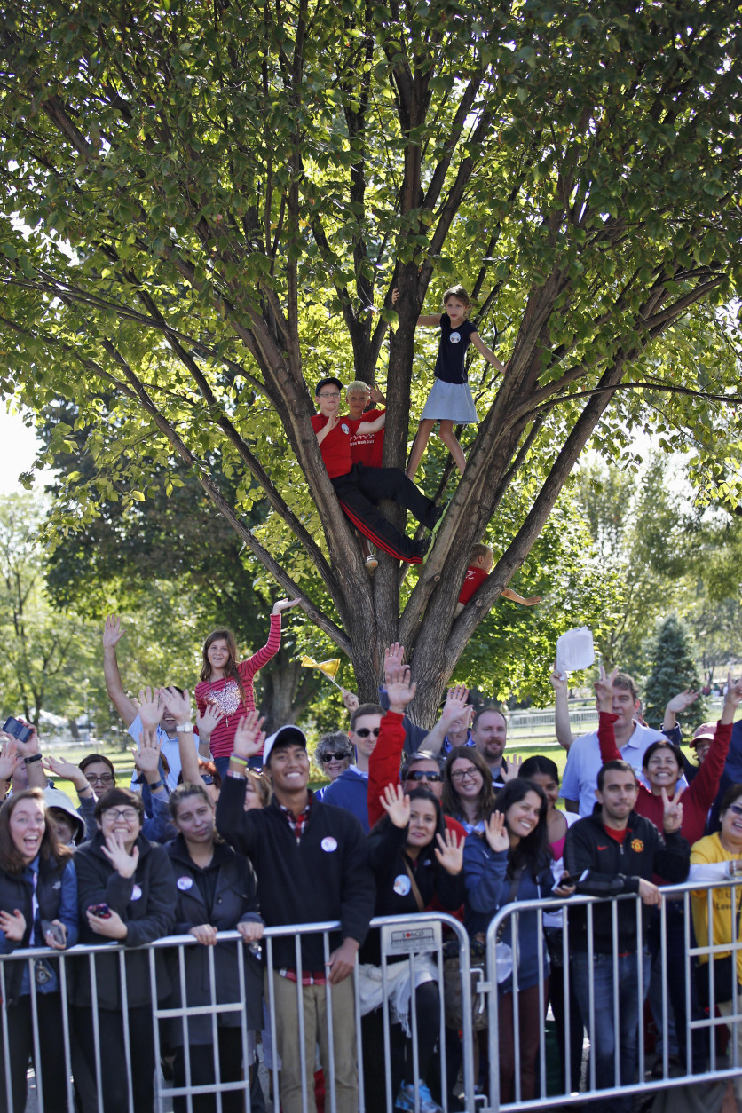 People wave and cheer before a parade for Pope Francis, Wednesday, Sept. 23, 2015 in Washington. Earlier, President Barack Obama hosted a state arrival for the pope at the White House. (AP Photo/Alex Brandon, Pool)