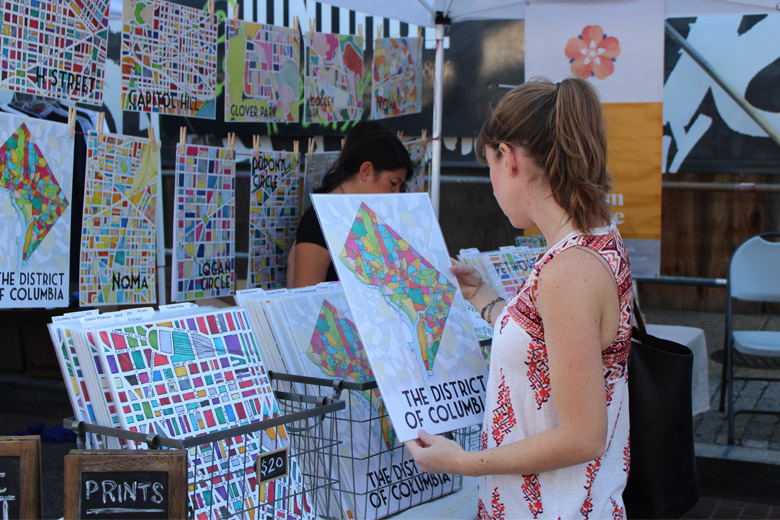 A festivalgoer checks out an illustrated poster at one of the stalls on H Street. (WTOP/Dana Gooley)