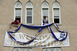 Brother Thomas Davenport, left, from Vienna, Va., and Brother Luke Hoyt, from Scio, Ohio, put up bunting around the sign in preparation for the upcoming visit by Pope Francis, Tuesday, Sept. 22, 2015, at the Dominican House of Studies, Tuesday, Sept. 22, 2015 in Washington. (AP Photo/Alex Brandon)