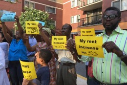 At a press conference Monday night, residents of the Hampshire Tower Apartments held up signs showing the big rent increases they're facing.  (WTOP/Michelle Basch)
