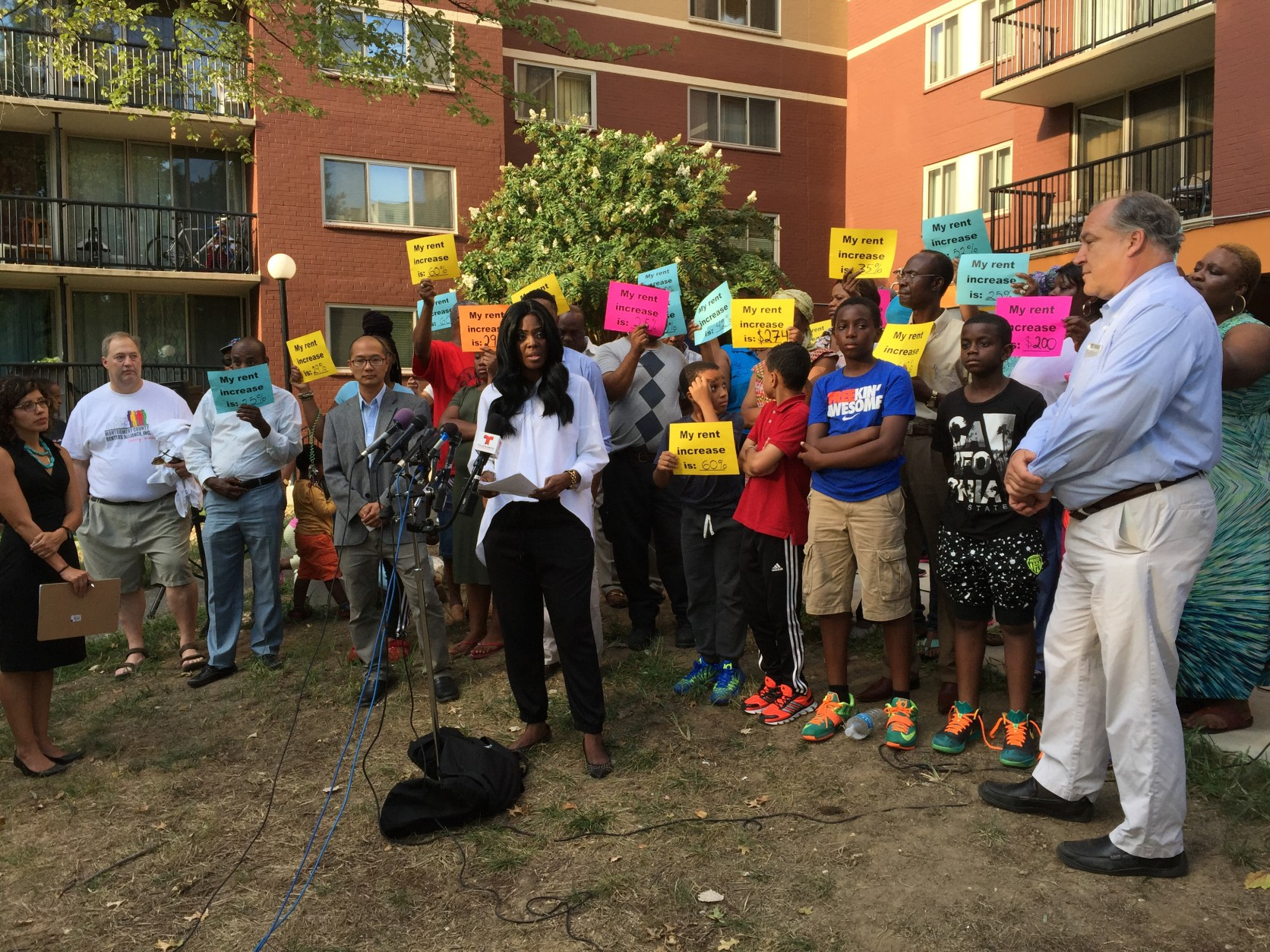 Residents hold signs as Acting President of the Hampshire Tower Tenant Association Margaret Buraimoh speaks. (WTOP/Michelle Basch)