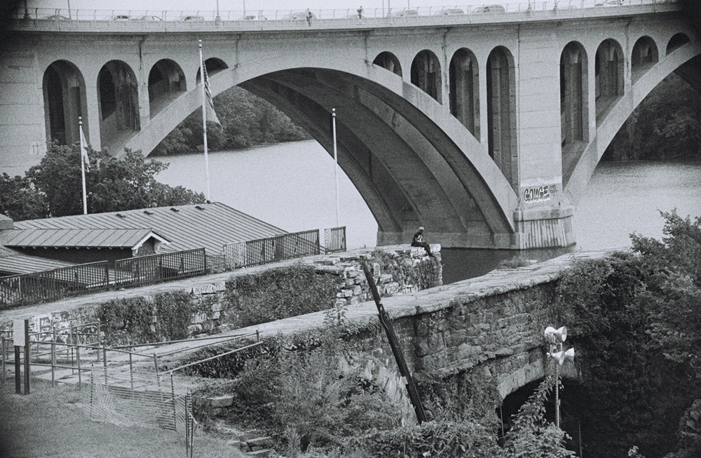The Aqueduct Bridge carried canalboats, horse-drawn wagons, and eventually trolley cars and automobiles across the Potomac River for nearly a century. It was demolished in 1933 but a remnant abutment still towers over the Capital Crescent Trail in Georgetown today. In the shadow of the Key Bridge, the stonework above the two surviving arches is mottled by graffiti. (WTOP/Dave Dildine)
