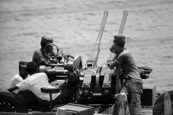 Cuban militiamen stand at battle stations on Havana's shoreline as the U.S. and the Soviet Union teeter on the brink of nuclear war over the presence of Soviet missiles in Cuba in October, 1962. The missiles are withdrawn after President John F. Kennedy (1917 - 1963) gives assurances to Soviet leader Nikita Krushchev (1894 - 1971) that the U.S. will not invade Cuba. (Photo by Alan Oxley/Getty Images)