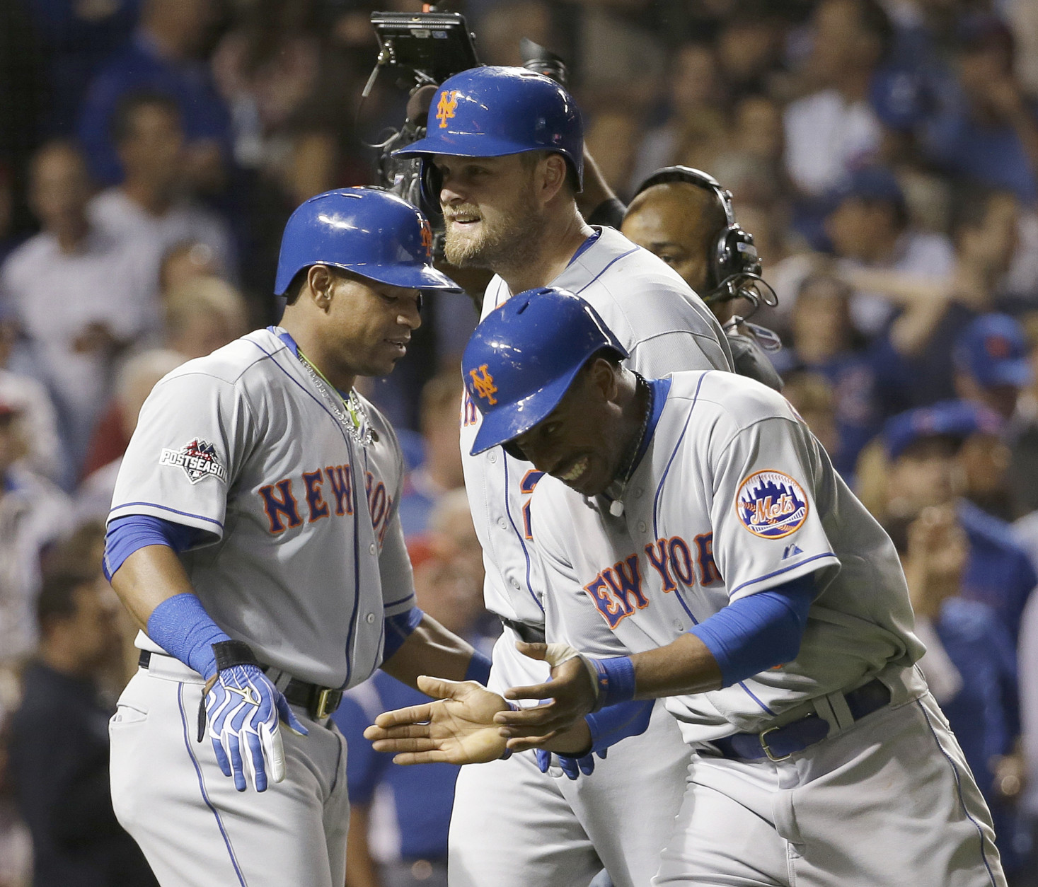 New York Mets' Lucas Duda is congratulated by Yoenis Cespedes, left, and Curtis Granderson, right, after hitting a three-run home run during the first inning of Game 4 of the National League baseball championship series against the Chicago Cubs Wednesday, Oct. 21, 2015, in Chicago. (AP Photo/David J. Phillip)