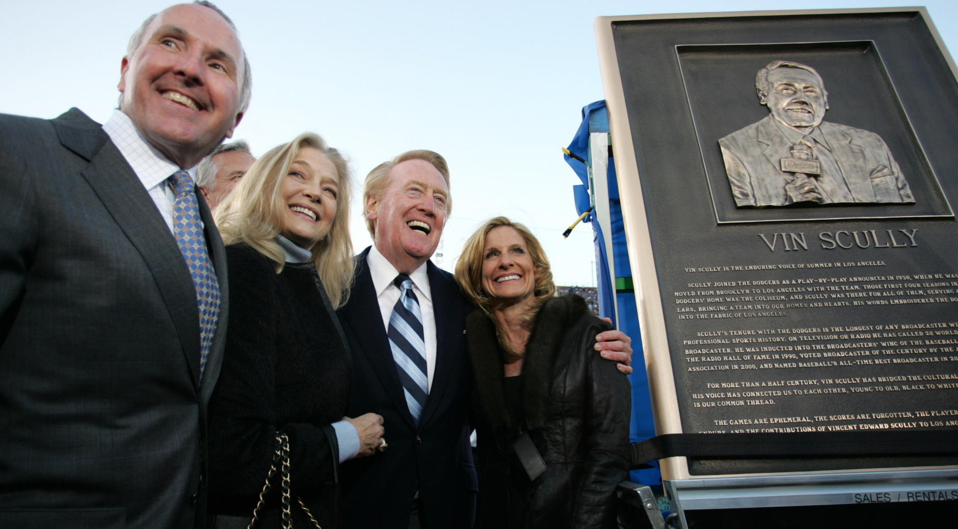 Los Angeles Dodgers owner Frank McCourt, left, wife Jamie, and Vin Scully, second from left, with wife Sandra, pose for photos next to a plaque honoring Scully before the start of an exhibition baseball game between the Los Angeles Dodgers and Boston Red Sox, Saturday, March 29, 2008 at the Los Angeles Coliseum in Los Angeles. The exhibition contest is part of the 50th anniversary of the Dodgers' move west from Brooklyn and is expected to draw a record crowd of over 115,000. (AP Photo/Branimir Kvartuc)