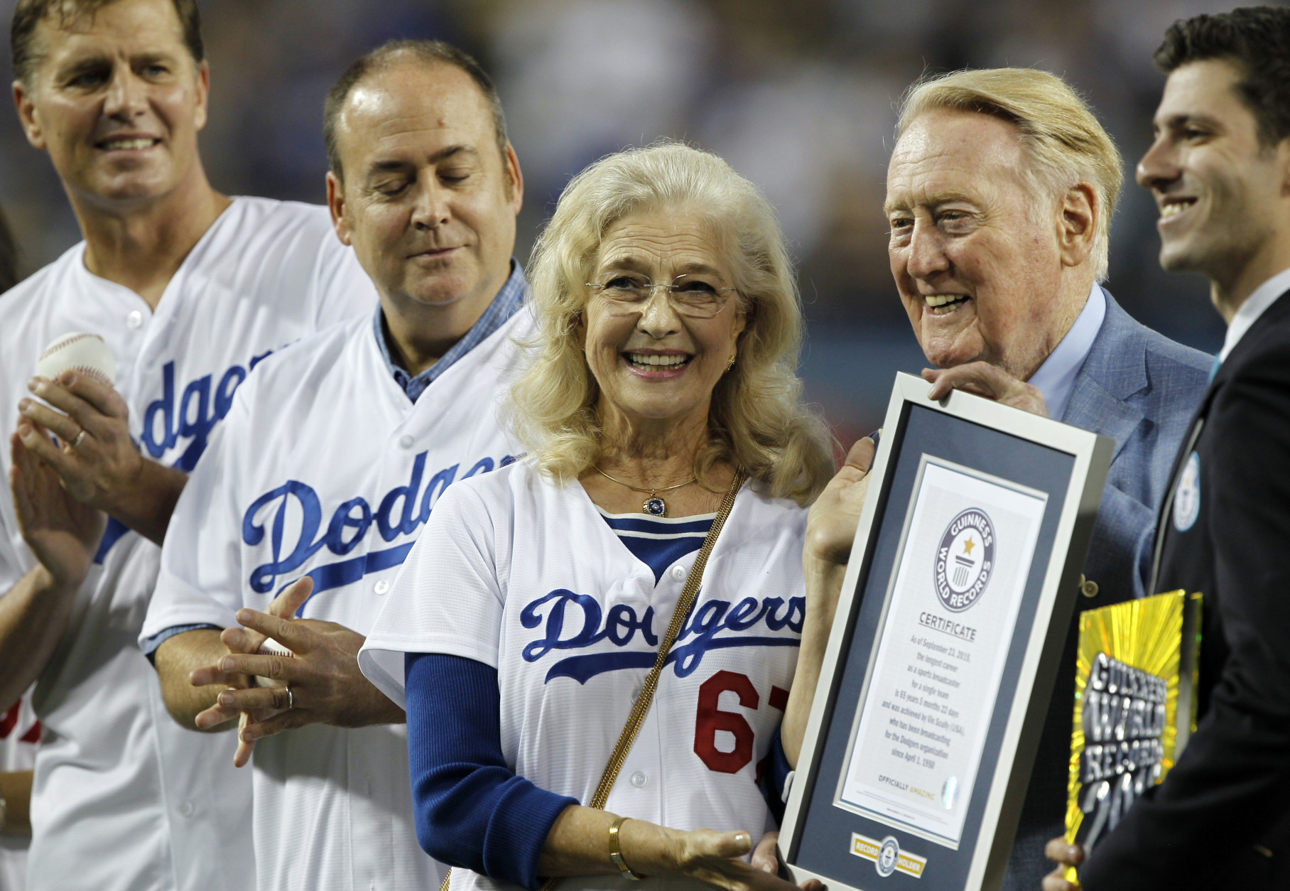 Los Angeles Dodgers broadcaster Vin Scully, second from right, is honored, with his wife Sandi Scuilly, and sons Kevin and Todd Scully, far left, before a baseball game against the Arizona Diamondbacks in Los Angeles, Wednesday, Sept. 23, 2015. Vin Scully was given a Guinness World Records certificate for the longest career as a sports broadcaster for a single team. (AP Photo/Alex Gallardo)