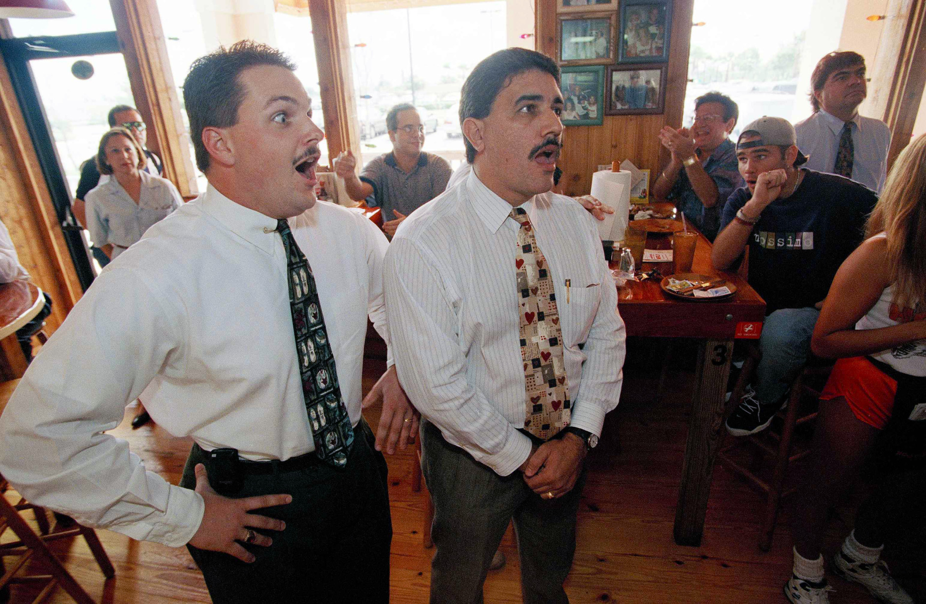 FILE - In this Oct. 3, 1995 file photo, Justin Barker, left, and his colleague Juan Borrego react as they hear the verdict of the O.J. Simpson trial from a Hooters restaurant in Miami. Barker was jubilant while Borrego had believed he was guilty beyond reasonable doubt. Simpson was acquitted for the June 1994 murders of his ex-wife and her friend. (AP Photo/Marta Lavandier)