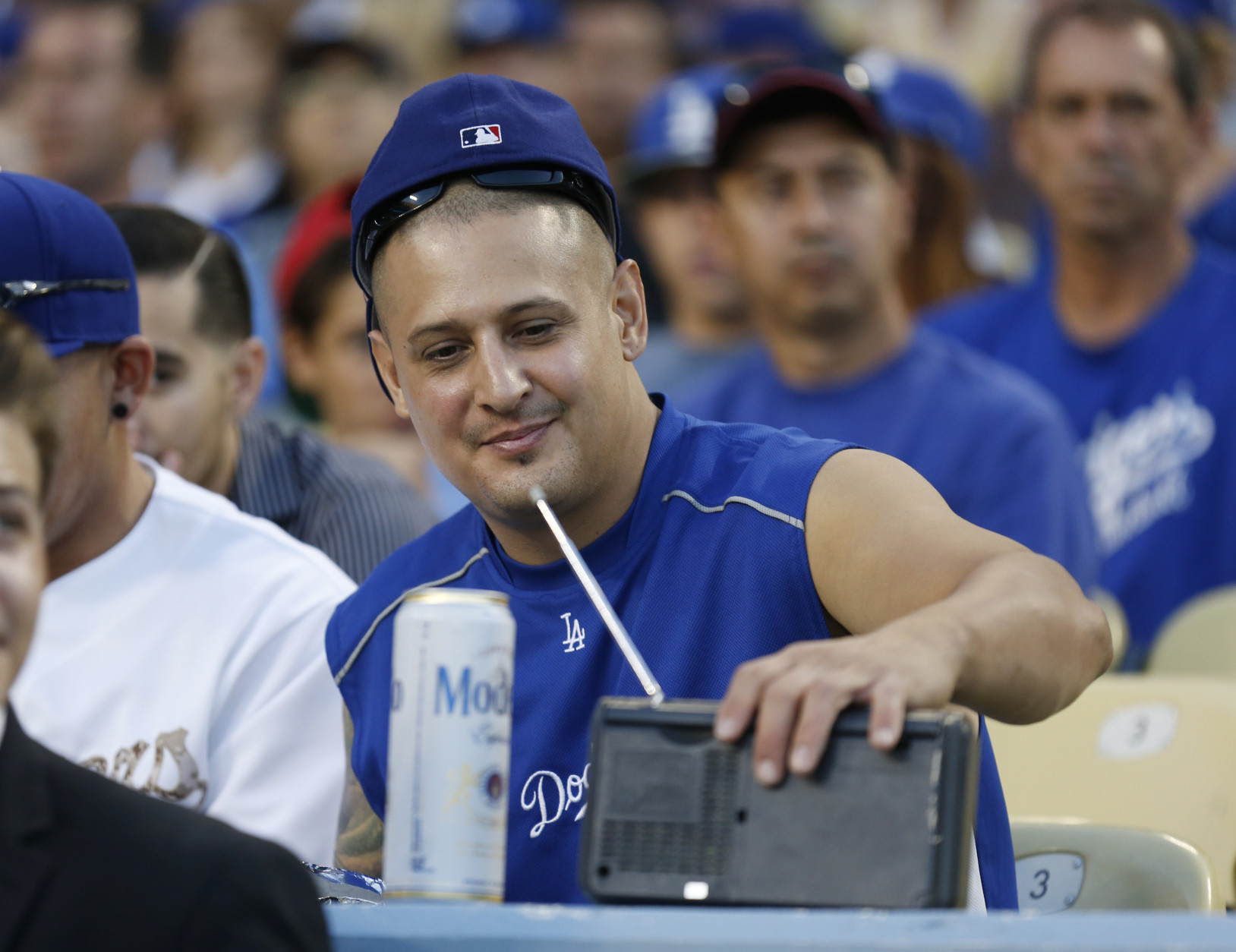 A Los Angeles Dodgers fan listens to announcer Vin Scully on a radio while attending a baseball game at Dodger Stadium against the Los Angeles Angels, Monday, August 4, 2014, in Los Angeles. (AP Photo/Danny Moloshok)