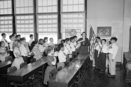 Holding the hand over the heart is the salute to the flag used in New York public schools. The old type military salute has been discontinued by a law passed in 1942.  This is a sixth grade class in P.S. 116 at 33rd street in Manhattan, Oct. 11, 1957. (AP Photo)