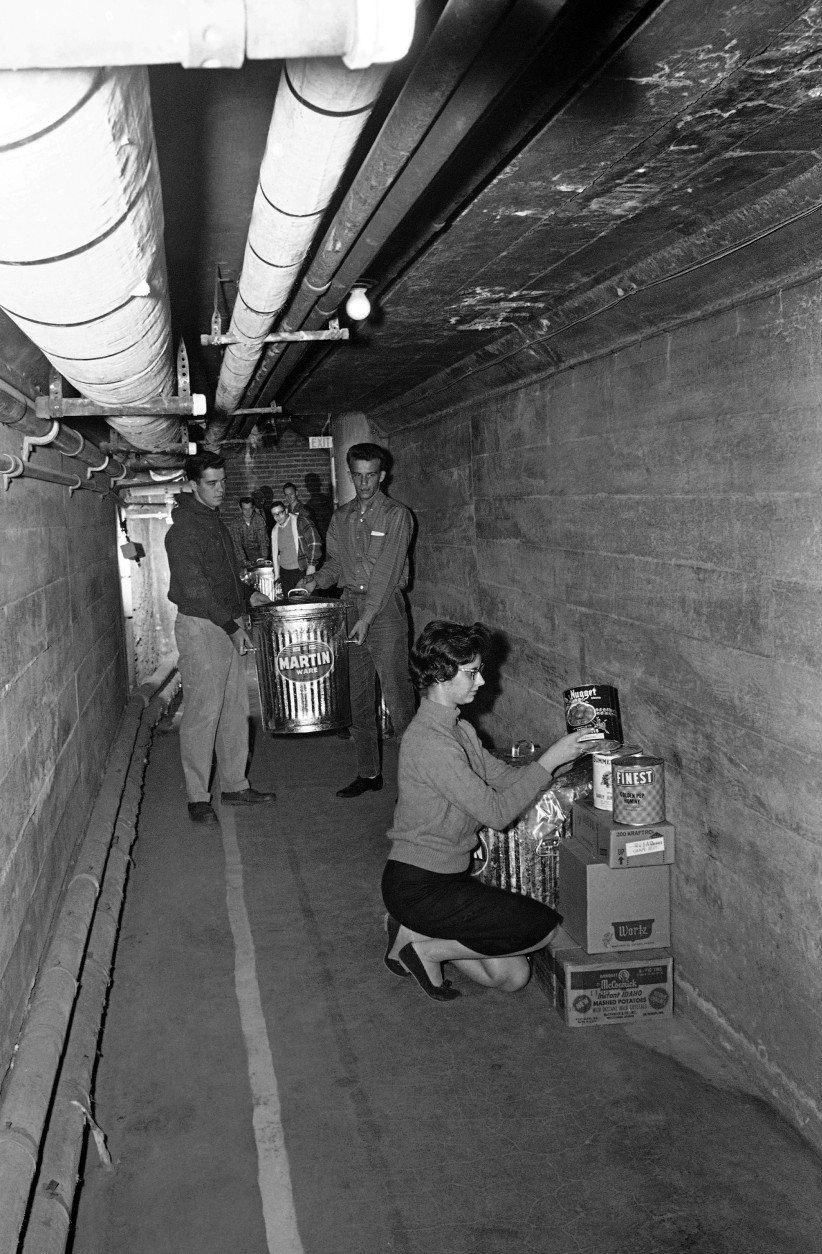 Students at National College in Kansas City begin stocking a tunnel under the campus with survival supplies shown Oct. 24, 1962. College officials said it was a precautionary measure against possible atomic attack. Irene Peters, 19, Canton, Mo., stacks canned goods. In background, Edgar Walden, left, Indianapolis, and Jim Potter, Kansas City, carry in water. The college is putting in a two-week supply of food, water and oxygen in two tunnels that connect the building. The school is a Methodist four-year college. (AP Photo/William P. Straeter)