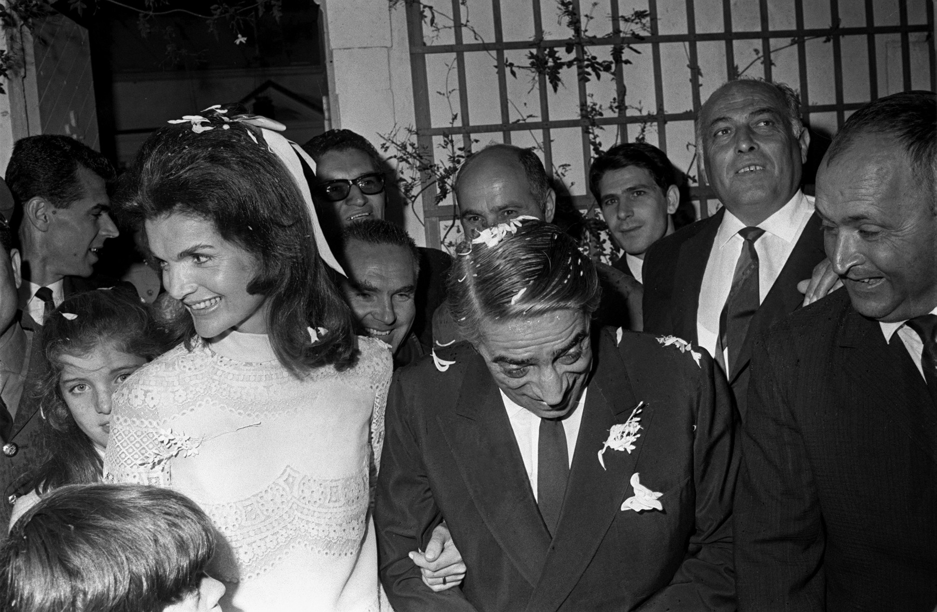 With daughter Caroline peeking over her right shoulder, Jacqueline Kennedy Onassis leaves the chapel with her new husband, Greek shipping magnate Aristotle Onassis, after their wedding on the Greek Island of Scorpios, Oct. 20, 1968.  (AP Photo/Jim Pringle)