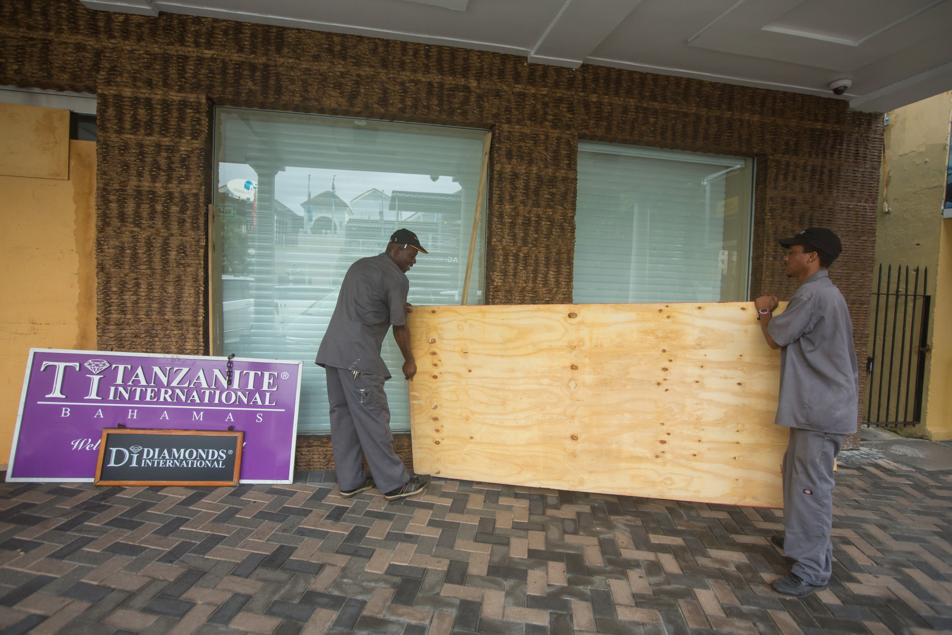 Perry Williams, 47, left, and Alaric Nixon, 28, carry a sheet of plywood as they cover the windows of the Diamond's International store, in preparation for the arrival of hurricane Joaquin in Nassau, Bahamas, Thursday, Oct. 1, 2015. Hurricane Joaquin unleashed heavy flooding as it roared through sparsely populated islands in the eastern Bahamas as a Category 4 storm, with forecasters warning it could grow even stronger before carving a path that would take it near the U.S. East Coast. (AP Photo/Tim Aylen)