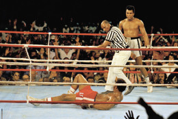 FILE - This is a  Oct. 30, 1974 file photo of Muhammad Ali, right, as he  stands back as referee Zack Clayton calls the count over opponent George Foreman, red shorts, in Kinshasa, Zaire.  Ali won the fight in Africa by a knock out in the 8th round. It was 40 years ago that two men met just before dawn on Oct. 30, 1974, to earn $5 million in the Rumble in the Jungle. In one of boxing's most memorable moments, Muhammad Ali stopped the fearsome George Foreman to recapture the heavyweight title in the impoverished African nation of Zaire. (AP Photo, File)