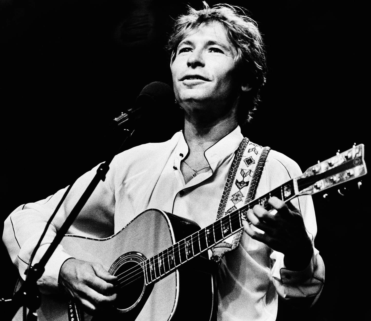 FILE - In this July 28, 1983 file photo singer John Denver strums his guitar as he performs during an outdoor concert on the Boston Common, Boston, Mass.  Denver was honored posthumously with a star on Friday, Oct. 24, 2014, on the Hollywood Walk of Fame in Los Angeles. Two of Denver's three children, Zak Deutschendorf and Jesse Belle Denver, accepted the star on behalf of the late singer's family.  Denver died tragically in a plane crash on Oct. 12, 1997. (AP Photo/Keith Jacobson, File)
