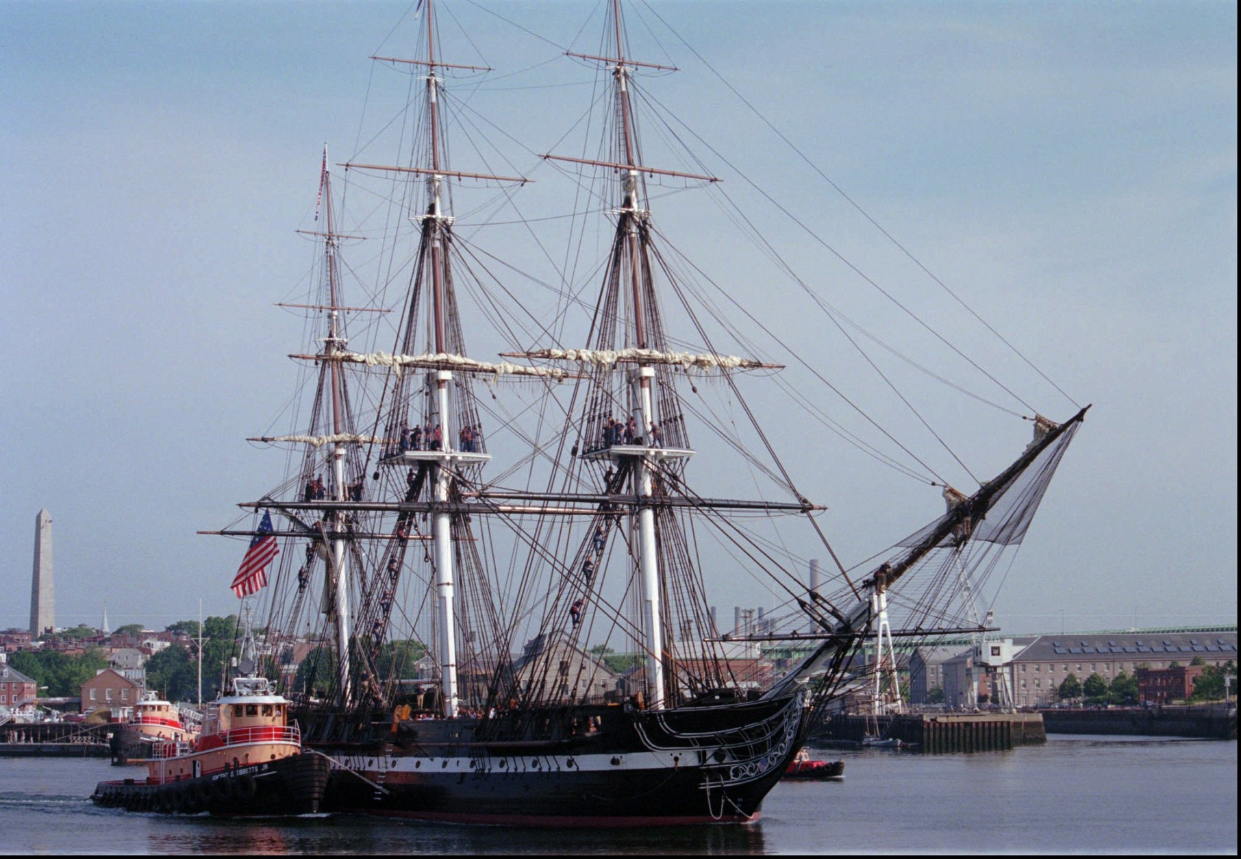 Crew members climb aloft to duty stations as the USS Constitution is carefully guided from its berth at the Charlestown Navy Yard in Boston, early Tuesday morning, July 8, 1997, as it is towed out of Boston Harbor for a day of sea trials in preparation for its 200th anniversary sail July 21, 1997. The July 21st sail celebration will be the ship's first under its own power sail in 116 years.(AP Photo/Isabel Leon)