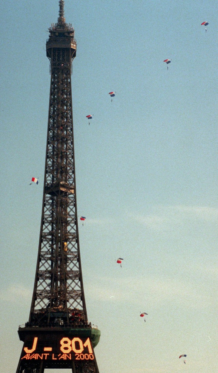 Some of 75 parachutists sail by Paris' Eiffel Tower Wednesday, Oct. 22, 1997 to celebrate the 200th anniversary of the first parachute jump. The first parachutist was a 28-year-old French physician named Andre-Jacques Garnerin. In 1797, he flew 1,300 feet above Monceau Park in Paris in a hot-air balloon, when he cut the balloon free and released a parachute that lowered him to the ground safely, except for a sprained ankle. Electric sign on the Eiffel Tower counts down the days until the year 2000. (APPhoto/Michel Lipchitz)