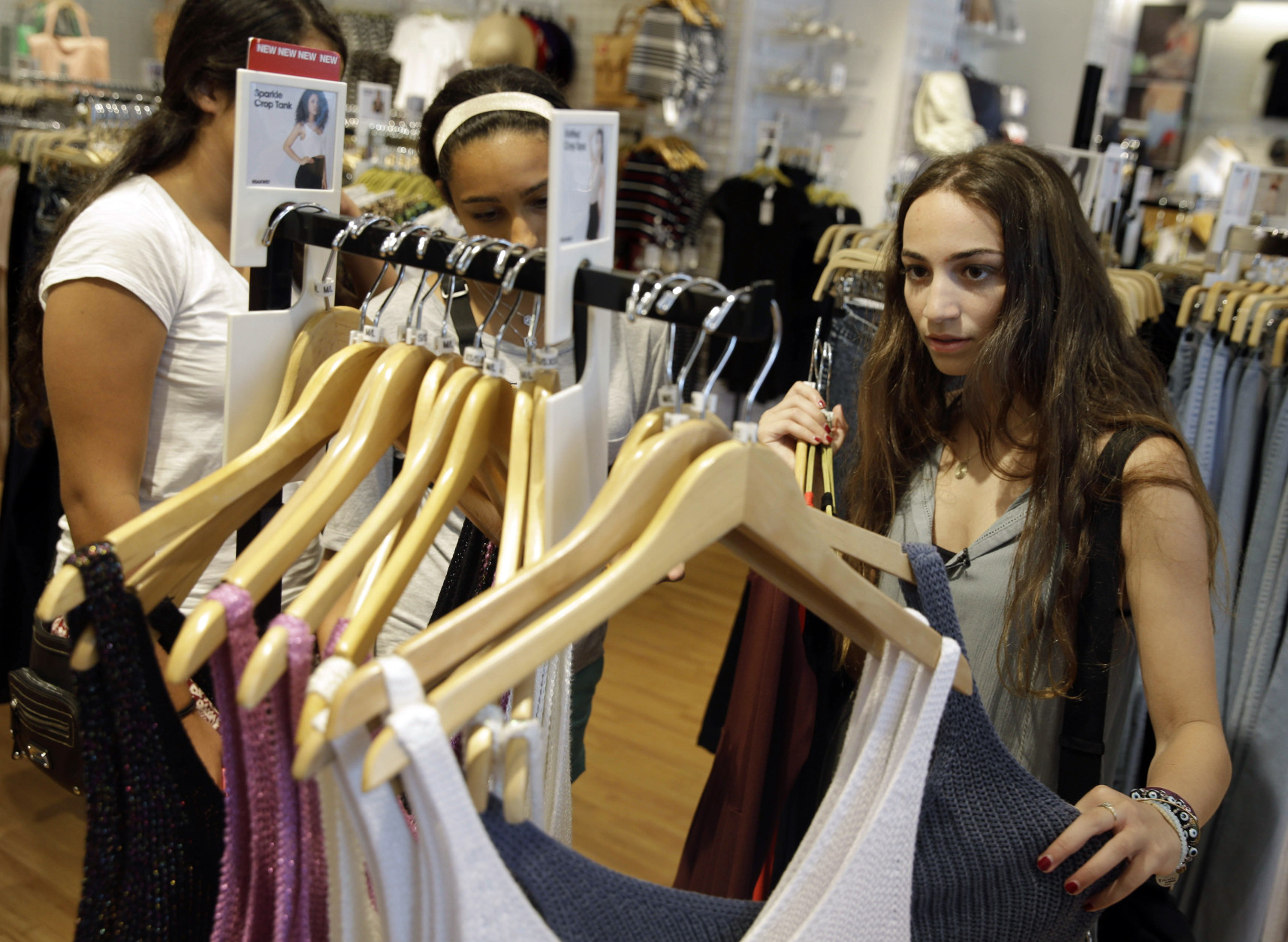 FILE - In this July 27, 2015, photo, Giulia Pugliese, 15, right, shops for clothes with friends at Roosevelt Field shopping mall in Garden City, N.Y. The Conference Board releases its October index on U.S. consumer confidence on Tuesday, Oct. 27, 2015. (AP Photo/Seth Wenig, File)